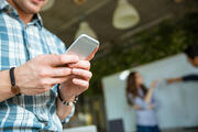 Closeup of hands of young man in checkered shirt using mobile phone while his partners arguing-1