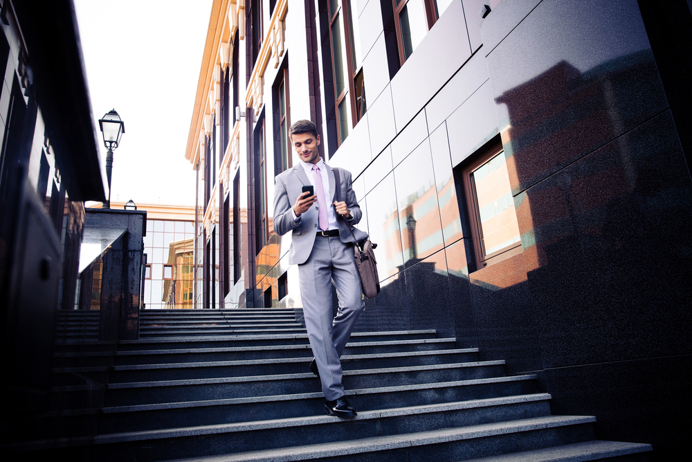 Happy businessman walking on the stairs and using smartphone outdoors-1