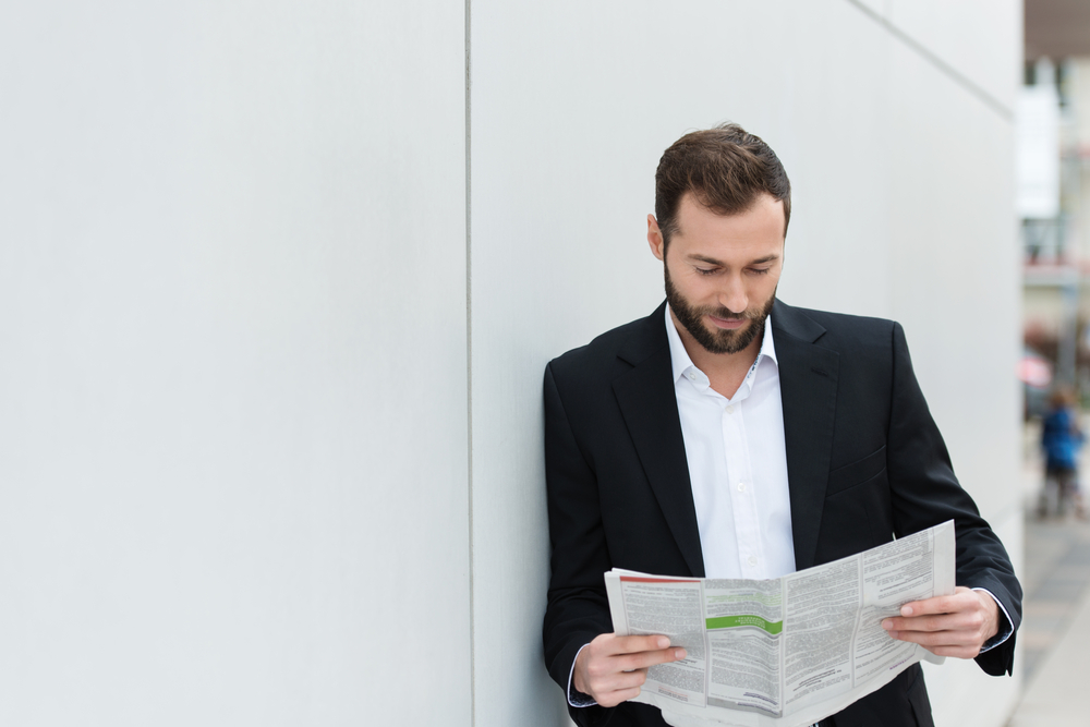 Businessman reading a newspaper on his lunch break as he leans against a white wall with copyspace