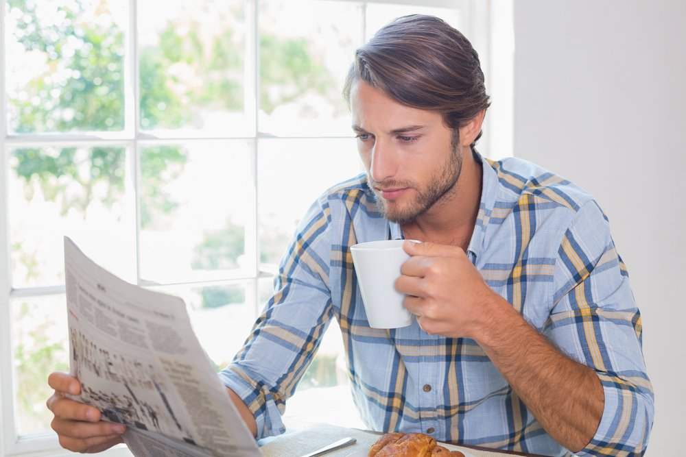Casual man having coffee while reading newspaper at home in the living room