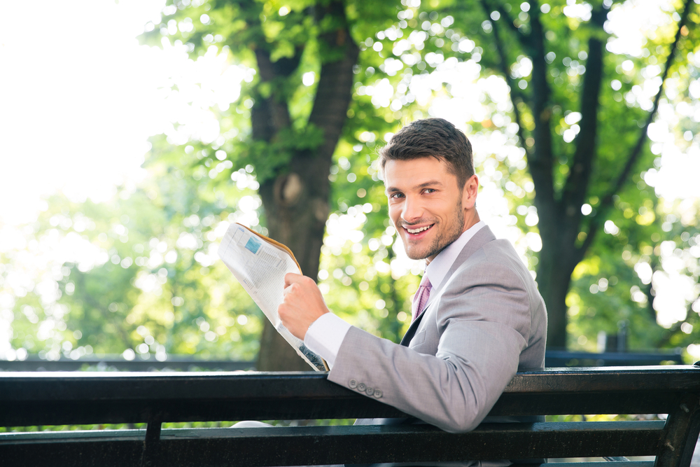 Happy businessman sitting on the bench with newspaper and looking at camera outdoors