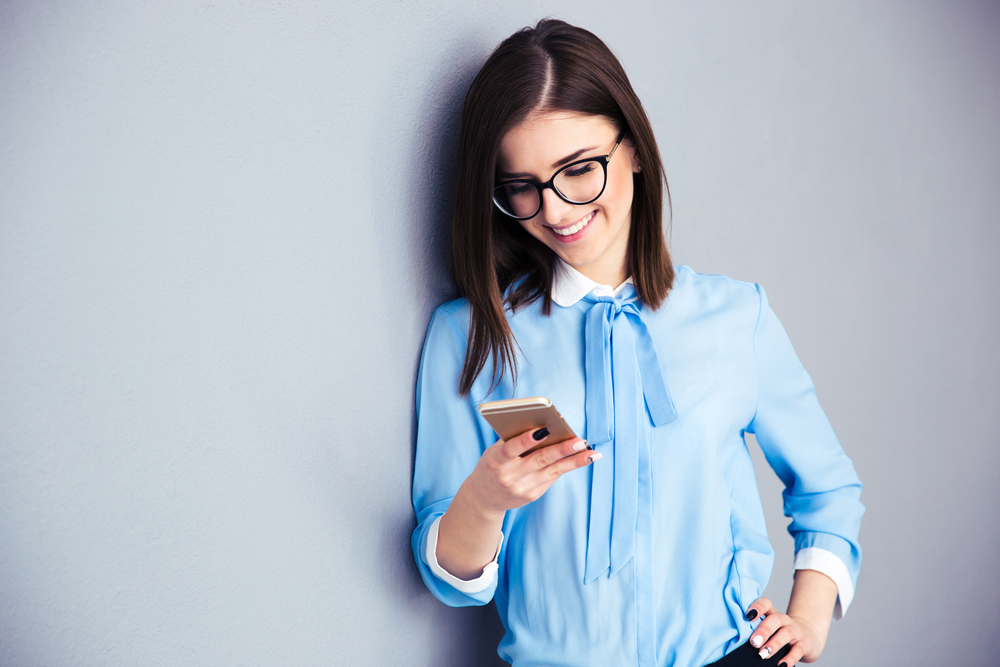 Happy businesswoman using smartphone over gray background. Wearing in blue shirt and glasses.